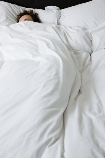 Man sleeping in bed covered under duvet elevated view