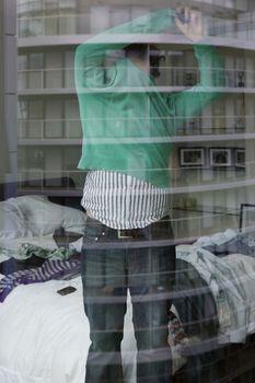 Man undressing in bedroom view through window