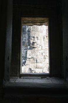 Stone Face Sculpture Seen Through Window of Ruins