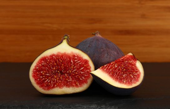 Close up one whole fresh ripe fig fruit with cut half and quarter slice on cutting board on table, low angle side view