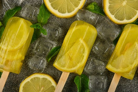 Close up frozen fruit juice popsicles with fresh lemon slices, green mint leaves and ice cubes on gray table surface, elevated top view, directly above
