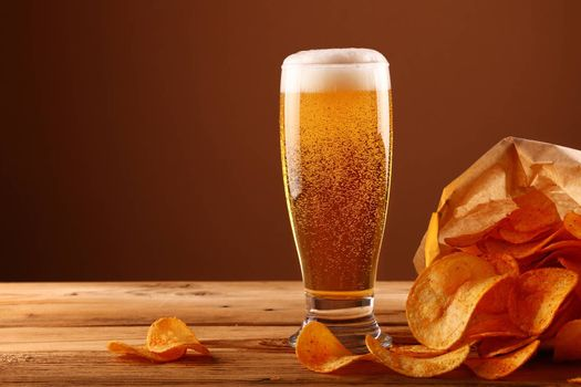 Close up one glass of lager beer with white froth and bubbles and paper bag of potato chips on wooden table over dark brown background with copy space, low angle side view