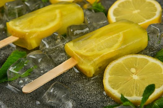 Close up frozen fruit juice popsicles with fresh lemon slices, green mint leaves and ice cubes on gray table surface, high angle view