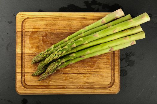 Close up bunch of washed fresh green asparagus on wooden cutting board with drops of water, elevated top view, directly above
