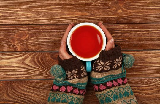 Close up two woman hands hold and hug big full cup of black tea or red fruit tea over brown wooden table, elevated top view, directly above