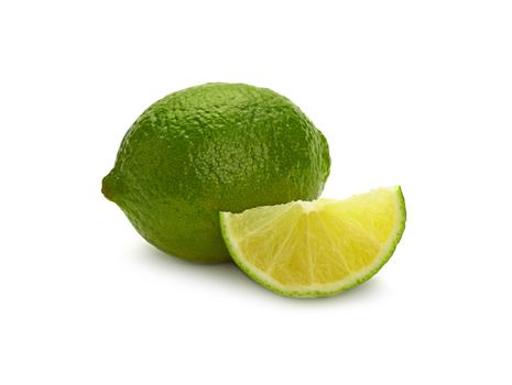 Close up one whole fresh green lime fruit and cut slice wedge, isolated on white background, low angle side view