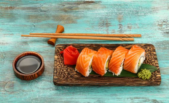 Close up one set of six Philadelphia sushi rolls with raw salmon served on palm wood plate on blue table, higgh angle view