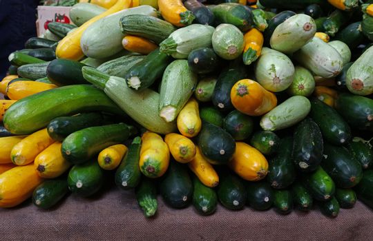 Close up fresh new green and yellow zucchini on retail display of farmers market, high angle view