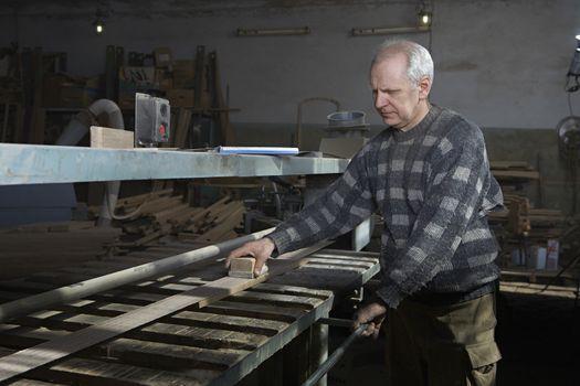 Carpenter Sanding Wood in Workshop