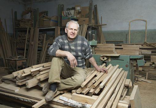 Carpenter Sitting on Wood Stacked in Workshop