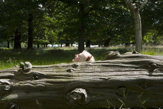 Woman Lying Beside a Tree Trunk