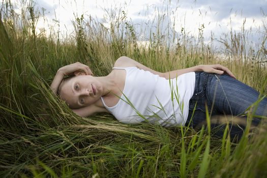 Serene young woman resting in meadow