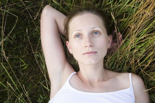 Serene young woman daydreaming on grass