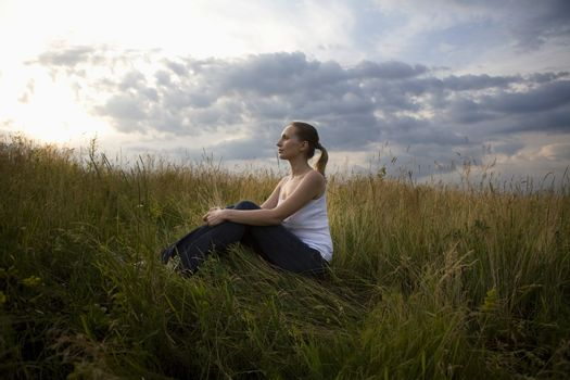 Serene young woman sitting in meadow