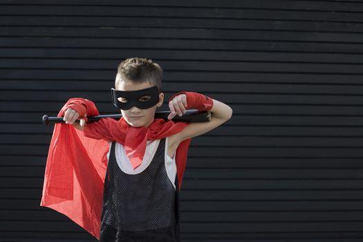Boy wearing Zorro costume with baseball bat