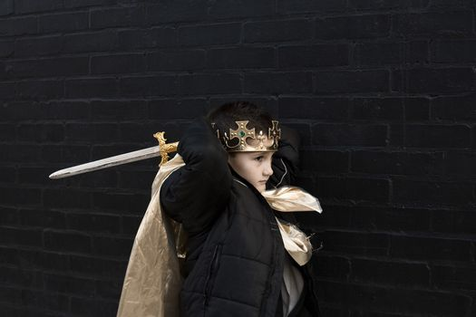 Boy dressed up as king with sword