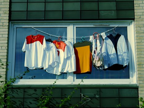 Shirts drying on clothesline outside window