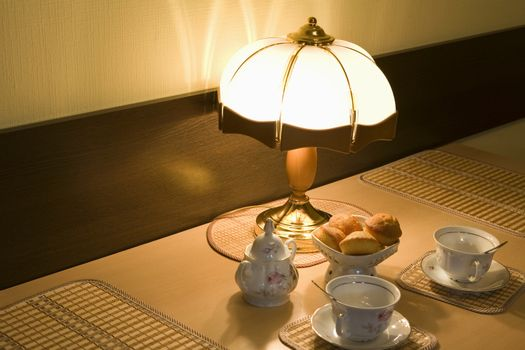 Lit lamp and teacups with scones