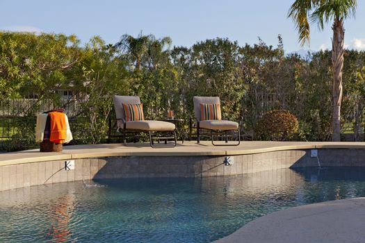 Chaise lounge chairs at poolside of manor house