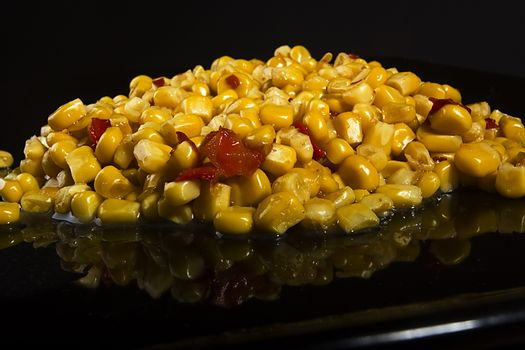 Tinned corn with pepper on a black plate