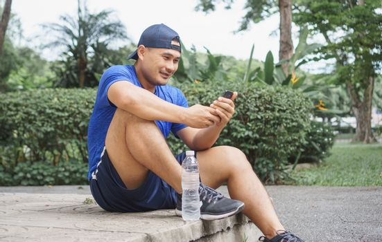 Asian adult men wear sportswear, sit in park after jogging and exercise. Sportsman is using smartphone technology to communicate with many people on Social media. Sports and fitness, healthy concepts