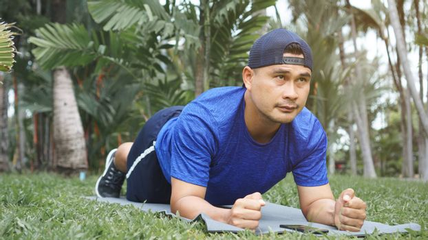 Mature Asian man fit and plank exercise on the grass in the park. sportsman wearing sportswear, fitness, and training outdoors. Sport and healthy for a balanced life