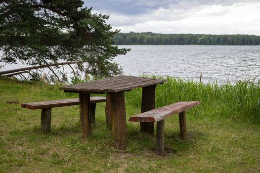Empty rustic wooden picnic table and chairs in a park at the edge of the sea with leafy green trees on the bank