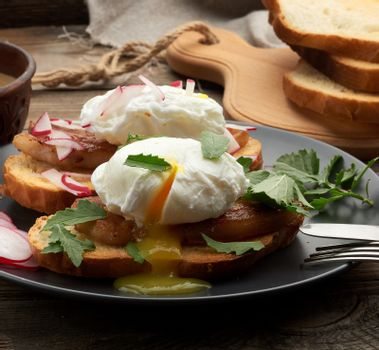 sandwich on toasted white slice of bread with poached eggs, green leaves of arugula and radish, morning breakfast on a brown wooden board, close up