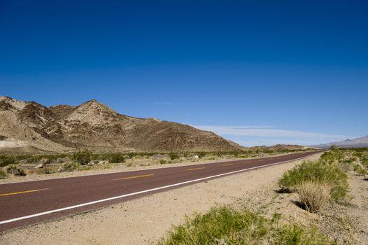 View of remote Kelbaker Road below clear blue sky