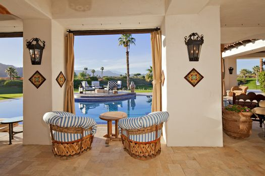 Patio with seating furniture at poolside in mansion