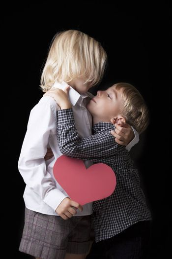 Sweet photo of a young boy kissing his blonde sister