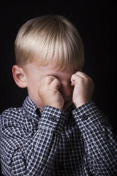 Portrait of little boy crying in studio