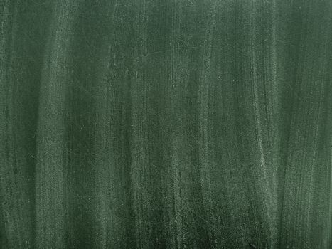 Texture of green school blackboard with white chalk traces. Black dirty chalkboard. Background with copy space.