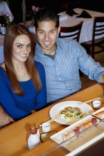 Portrait of a happy young couple eating Japanese cuisine in restaurant