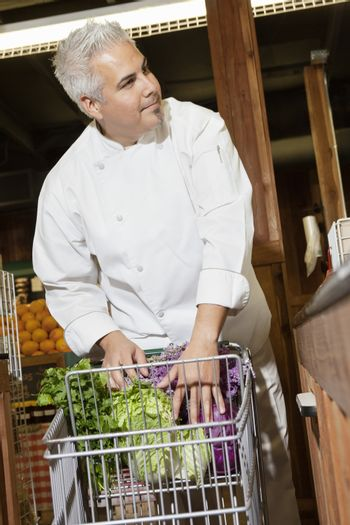 Mid adult chef with vegetables in shopping cart