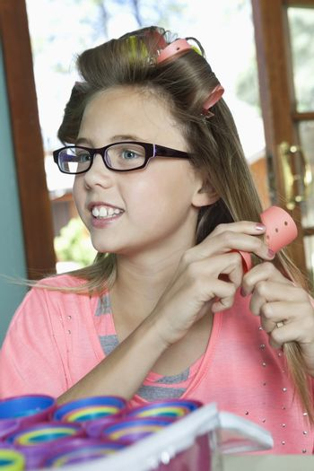Little girl curling hair with rollers