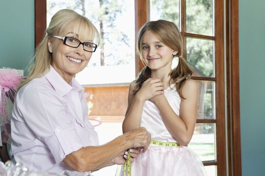 Grandmother measuring granddaughter's waist with tape