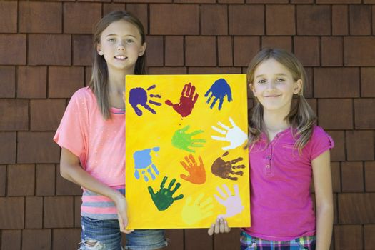 Girls showing colorful multiple hand prints against brick wall
