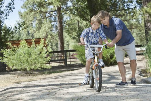 Father training son to ride a bike