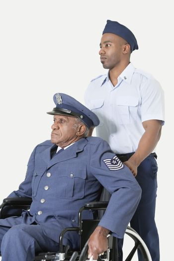 Male cadet assisting senior air force officer in wheelchair over light gray background