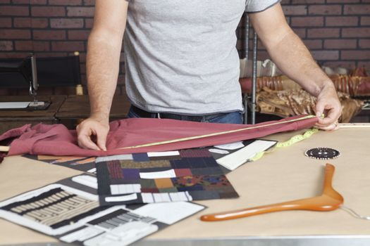 Midsection of male fashion designer taking measurement of shirt