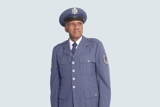 Senior male US Air Force officer standing over light blue background