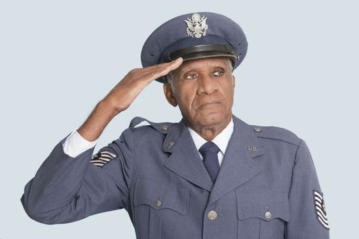 Portrait of a senior male US Air Force officer saluting over light blue background