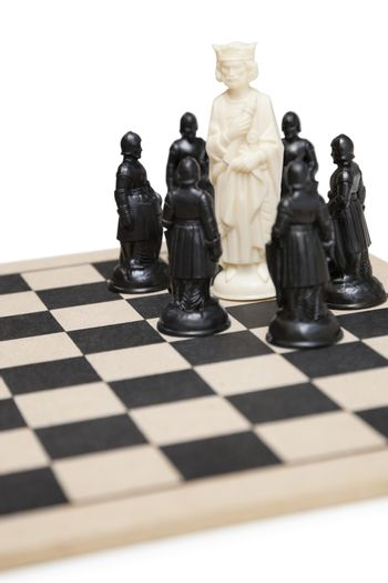 Chess game with king surrounded by black pawns