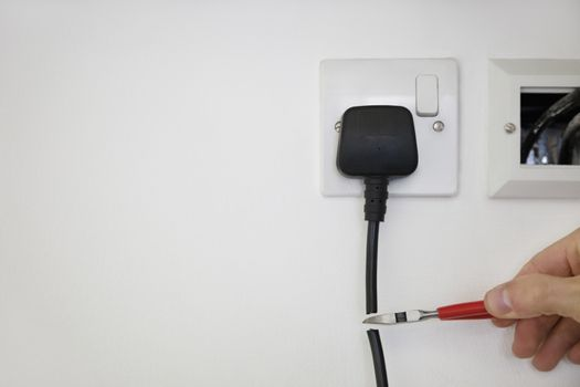 Cropped shot of hand cutting electrical cord attached to outlet on white wall
