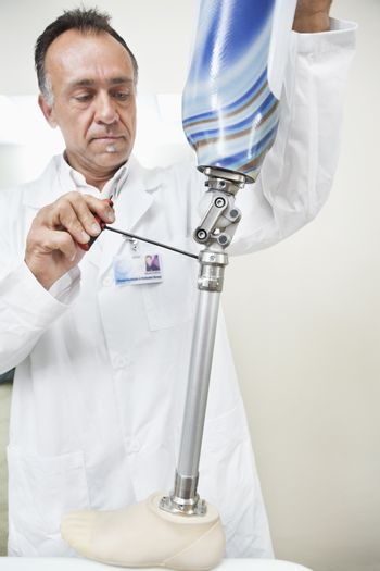Mature technician working on prosthetic device