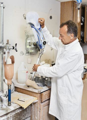 Mature technician working on prosthetic foot