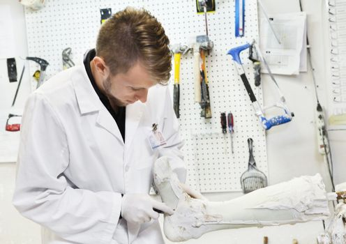 Young male worker working on prosthetic limb in workshop