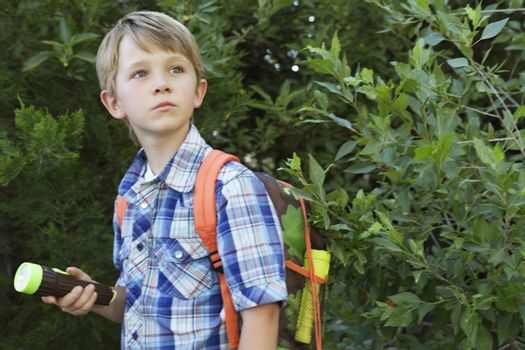 Boy with backpack and torch in front of plants