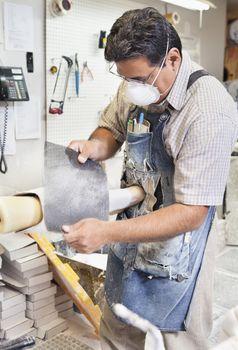 Mature male worker polishing prosthetic limb in workshop